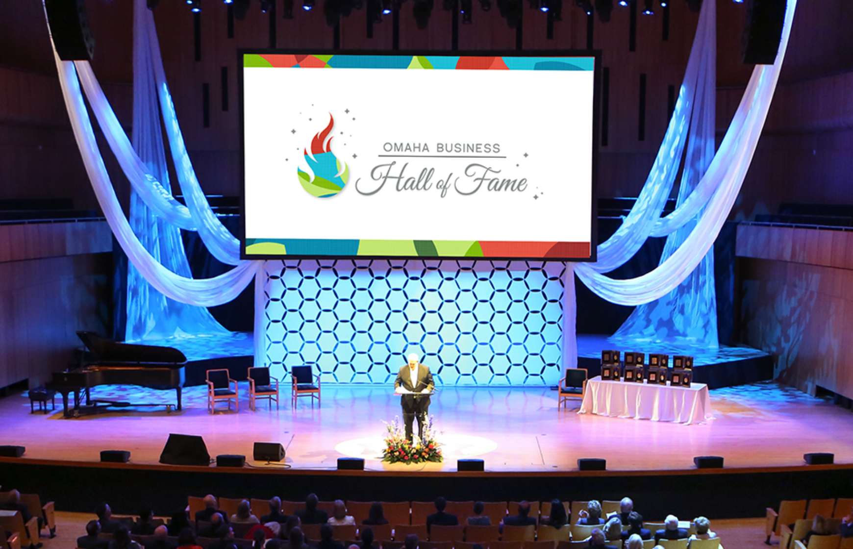 Man on stage at a podium during Omaha Business Hall of Fame