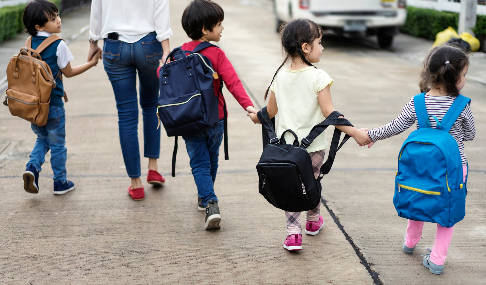 woman walking hand-in-hand with four young children