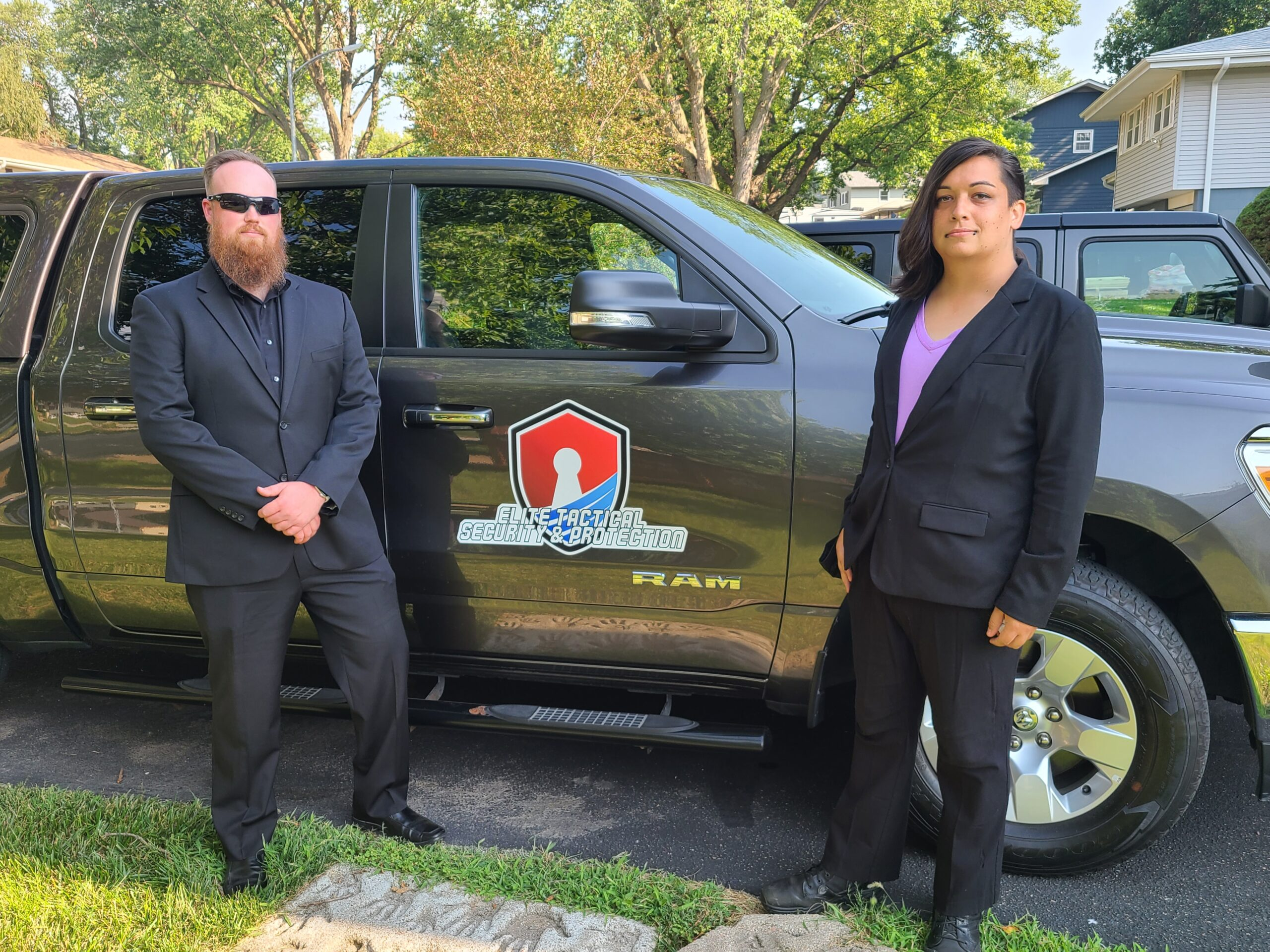 Two private security guards posing in front of an SUV with the Elite Tactical logo.